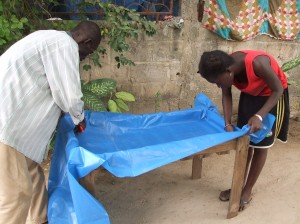 Step 1: Mamadou and Nafi line the table with voile plastique